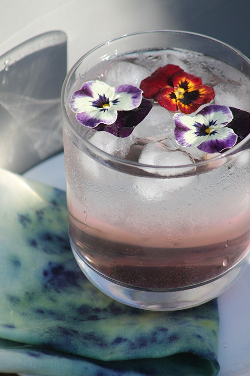 red pansy and purple violets delicately garnishing the top of a drink