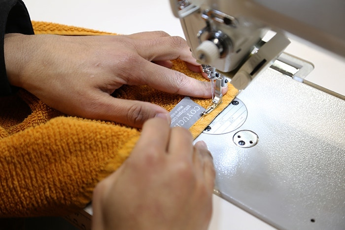 person sewing a Coyuchi label onto an Air Weight towel