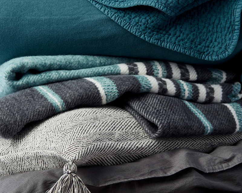stack of cascade blanket, flannel sheets, mariposa blanket, presidio pillow cover and sateen sheets