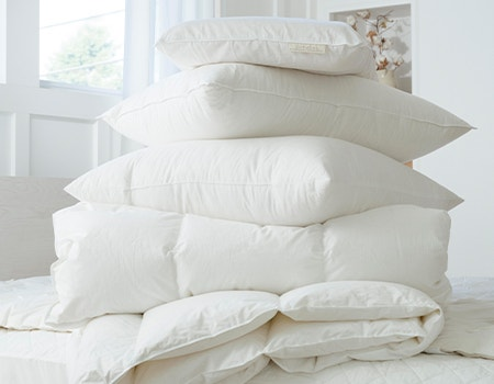 Stack of Coyuchi bed basics on unmade bed