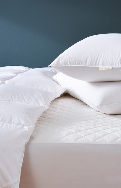 bedding basics on a bed including down pillows, organic mattress pad, and three seasons duvet comforter