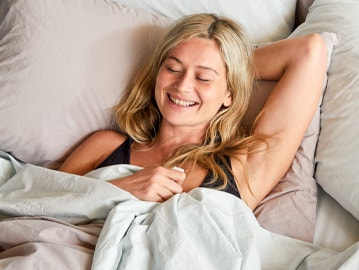 woman stretching in bed with organic relaxed linen bedding