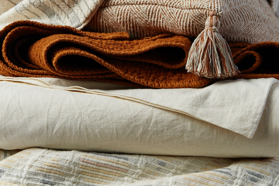 stacked organic blankets, organic sheets, and pillow covers in undyed and rust