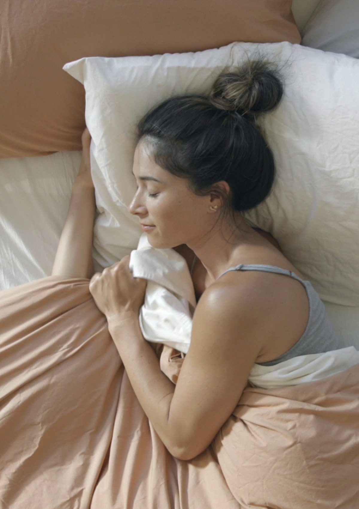 Woman resting in bed made with Organic Crinkled Percale Sheets