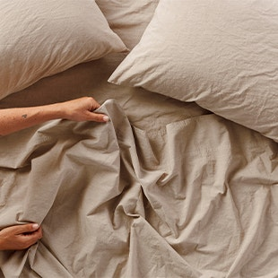 overhead of person making a bed with Organic Crinkled Percale™ Sheets