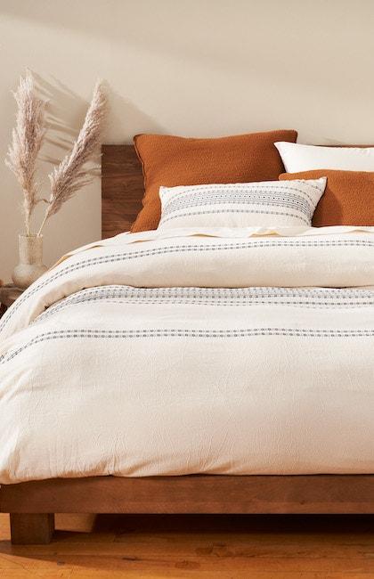 Rippled Stripe Organic duvet cover styled with rust Cascade Organic Shams