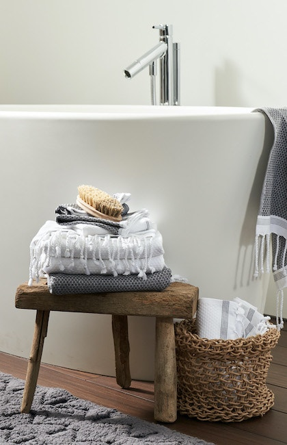 Air weight organic towels stacked in a bathroom featuring Sycamore Rug