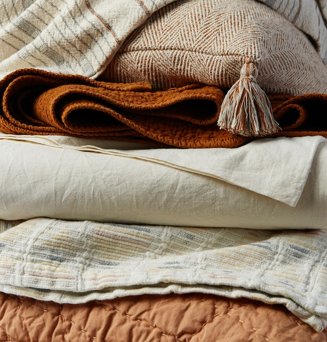 stack of organic bedding, blankets and pillow covers in a rust color story