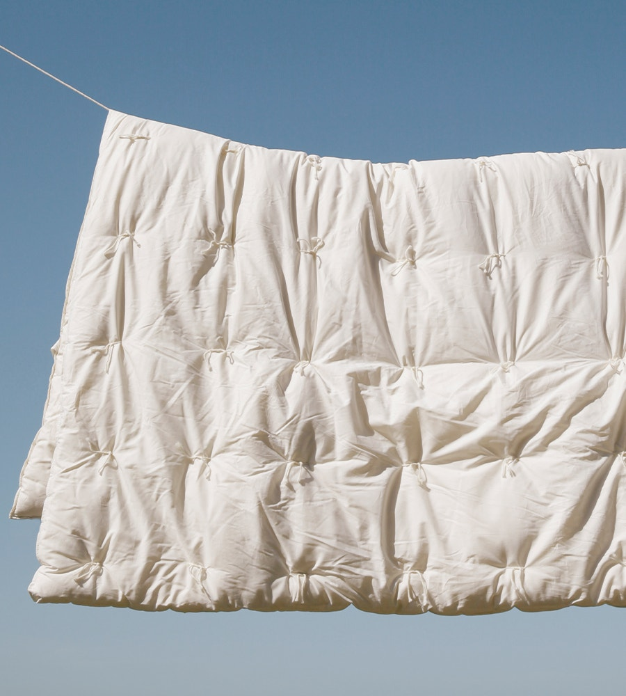 Climate Beneficial Wool Duvet Insert hanging on string above the ocean