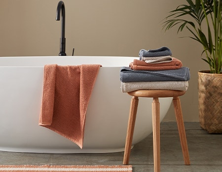 Stack of Air Weight Organic Towels on stool, with one towel hanging on edge of bathtub