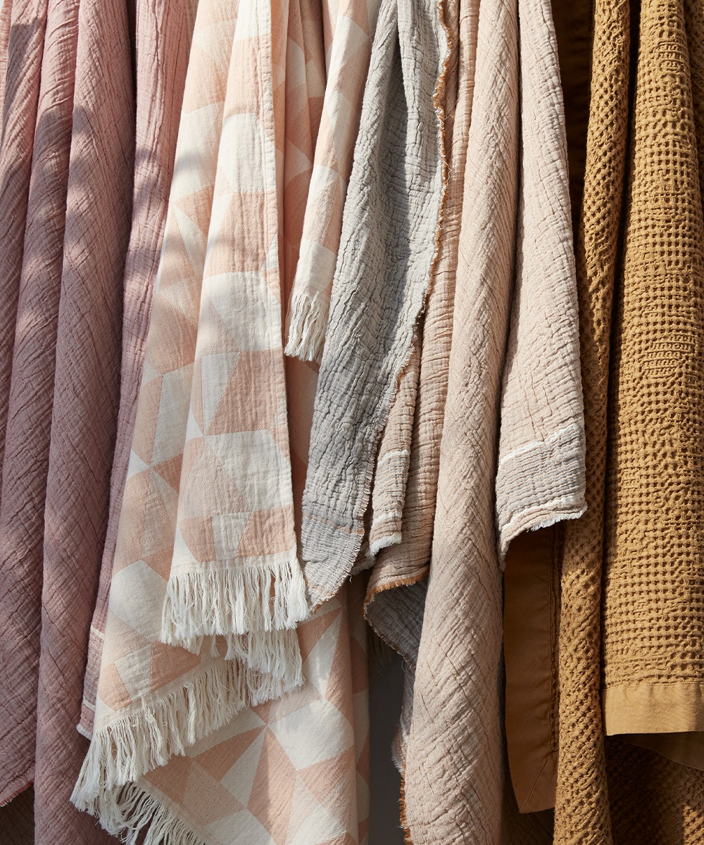 warm toned blankets hanging on a wall