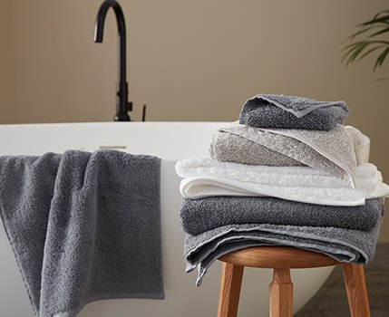 Cloud Loom Organic Towels resting on stool near bathtub