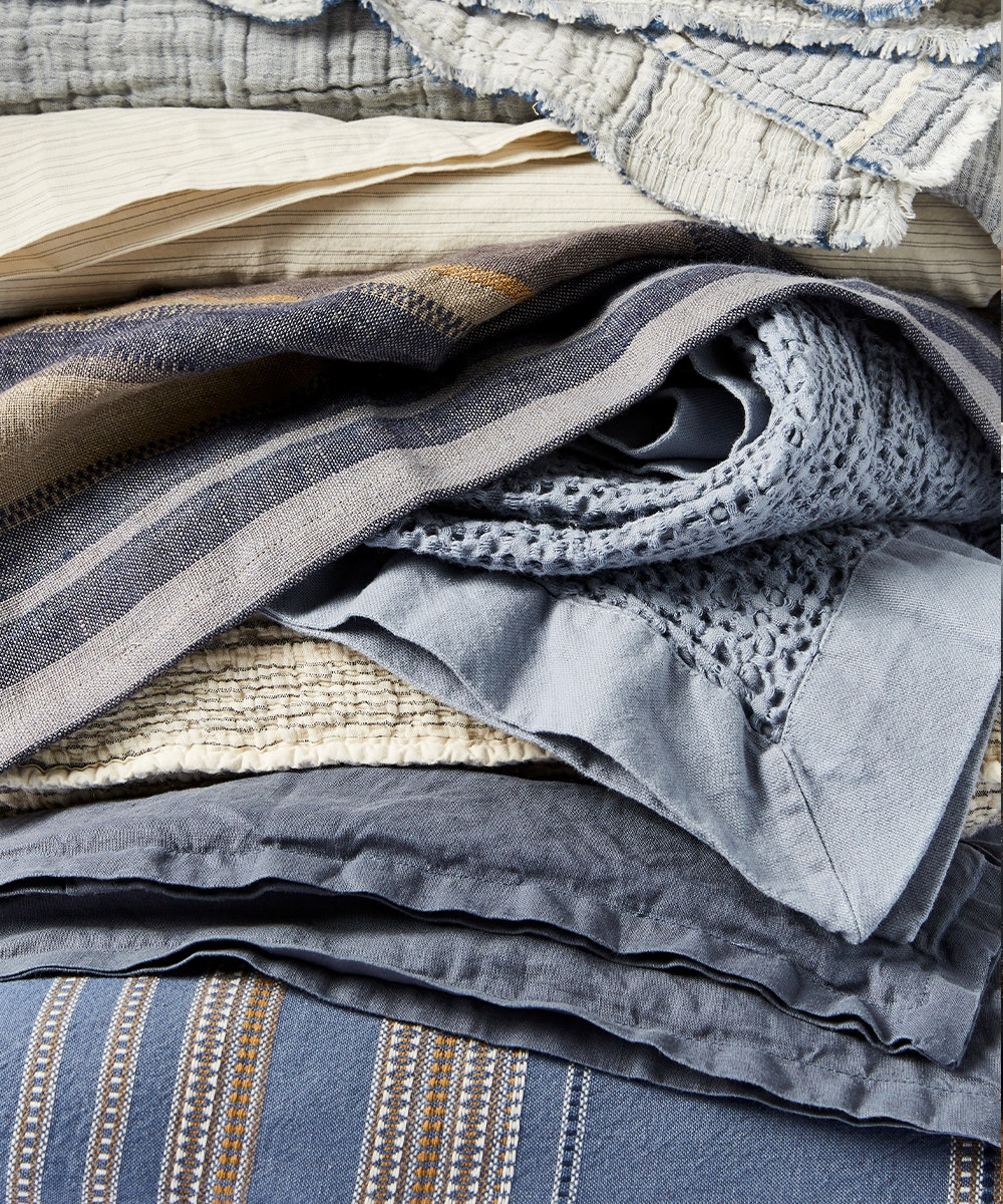 stack of various blue toned bedding