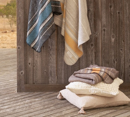 a variety of colors of the Diablo Wool Throws against a wood backdrop