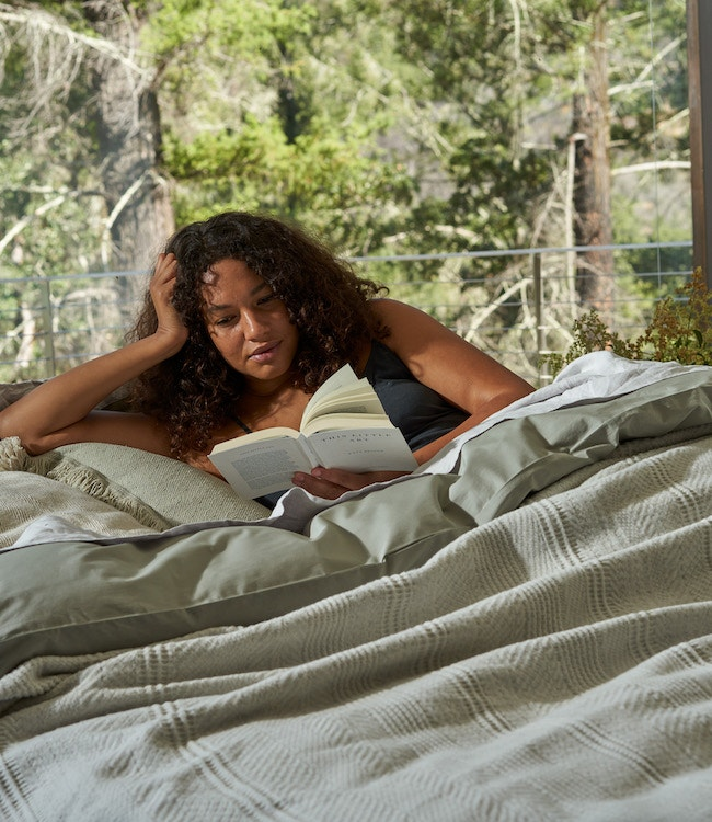woman reading in percale bedding