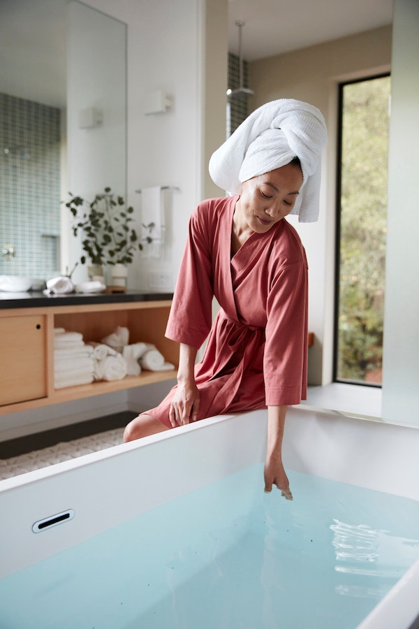 Woman sitting by bathtub wearing a Solstice Organic Kimono Robe with her hair wrapped in an Air Weight Organic Towel