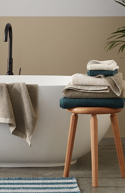 Stack of Temescal Organic Towels on stool, with one towel hanging on edge of bathtub