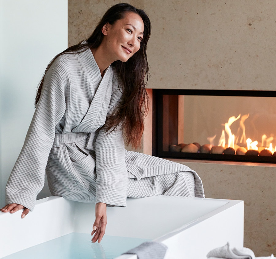 Woman sitting on edge of tub wearing the Unisex Organic Waffle Robe