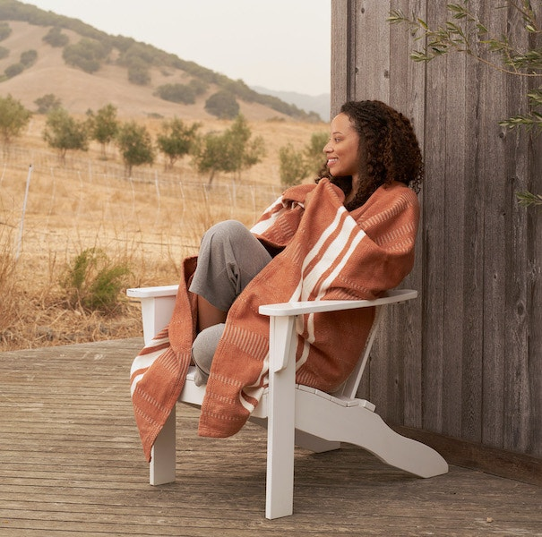 Woman sitting outside wrapped in a Cirrus Supersoft Organic Cotton Throw