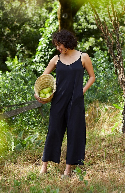 woman in solstice organic romper holding a basket of apples