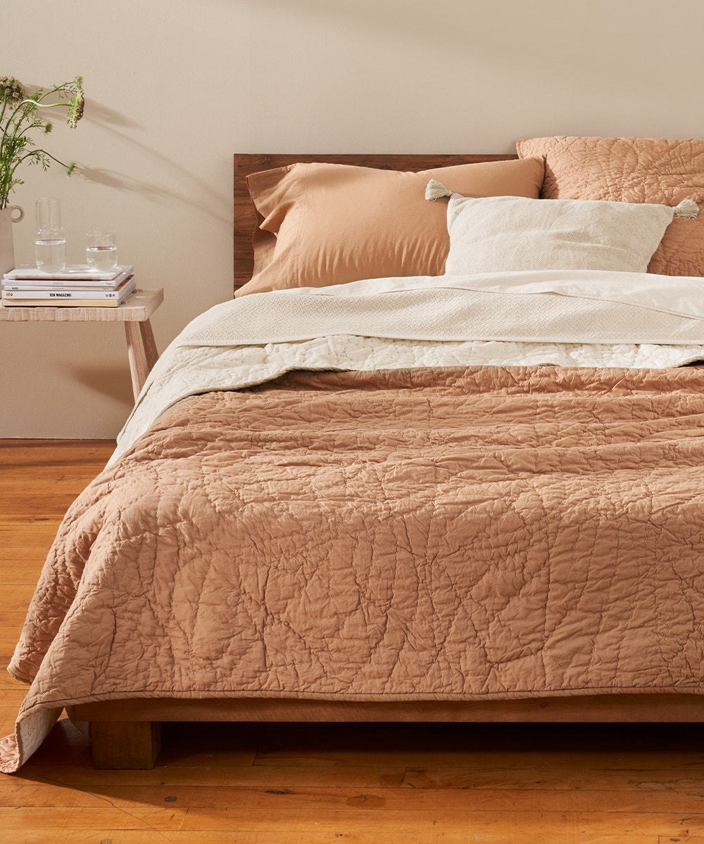 Manzanita Quilt in Ginger on a bed