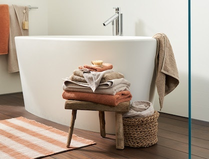 Stacked Air Weight Organic towels on a stool in a bathroom with Sycamore rug