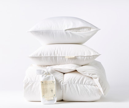 stack of pillows on top of a three season down duvet insert and a package of organic pillow protectors