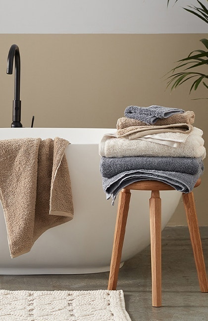 Stack of Cloud Loom Organic Towels on stool, with one towel hanging on edge of bathtub