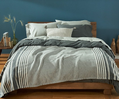 Cloud brushed organic flannel duvet cover and sheets on a bed layered with a warm mariposa supersoft organic cotton blanket