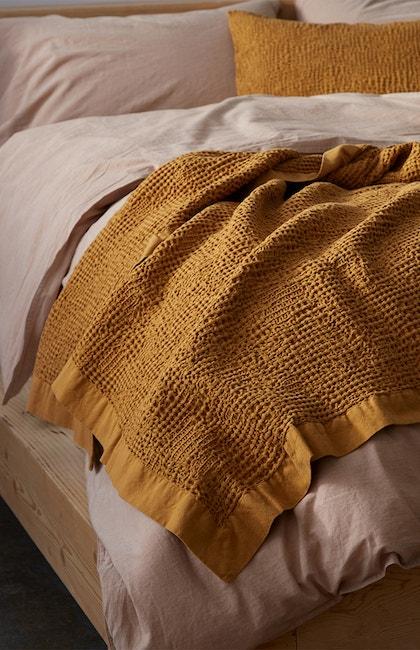 Reyes Organic Waffle Blanket draped over Organic Crinkled Percale Duvet Cover