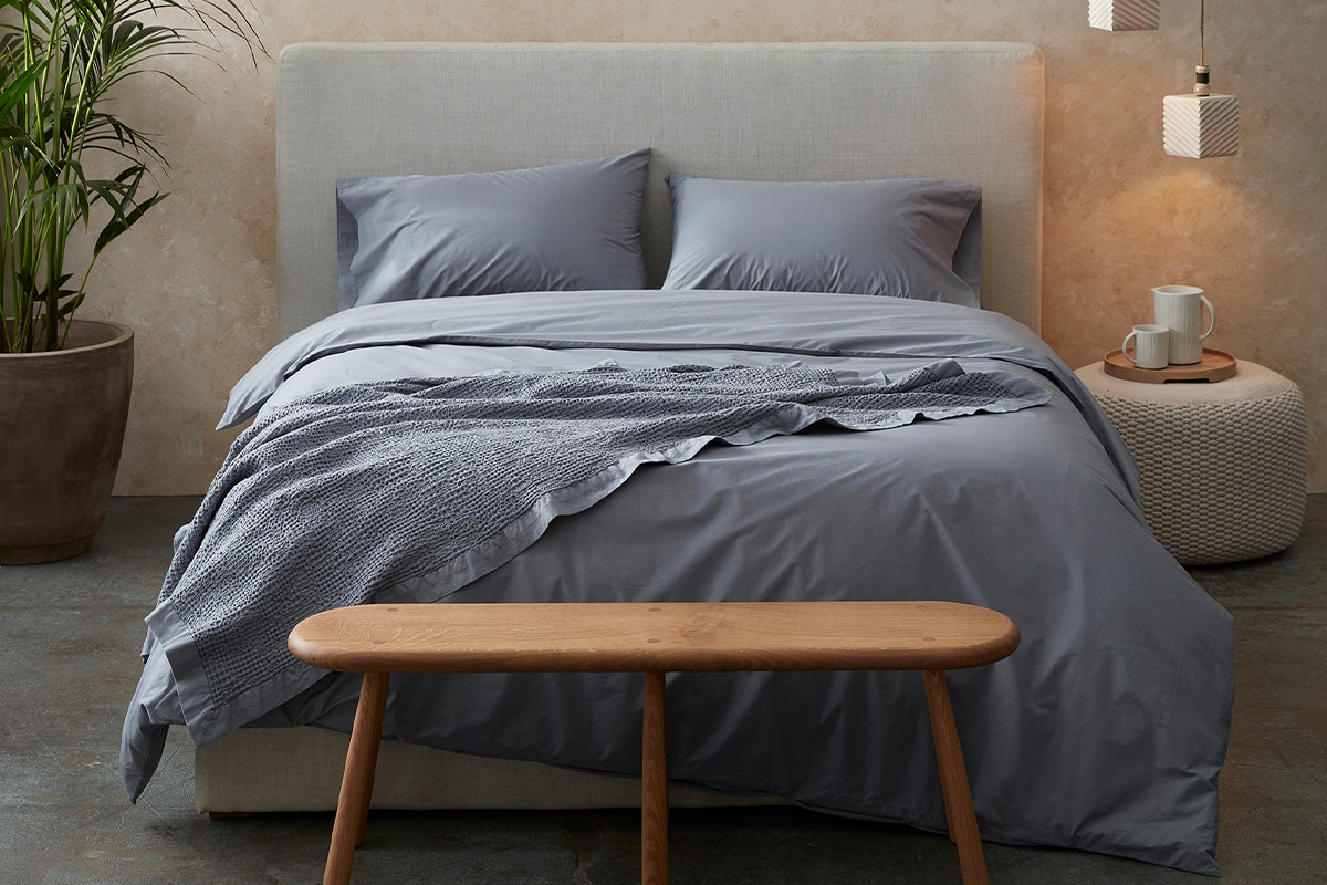 a bed in a room with a steel blue 300 Thread Count Organic Percale Duvet Cover and steel blue Reyes Organic Waffle Blanket