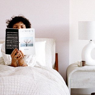 woman reading a book in a bed with the Miramar blanket