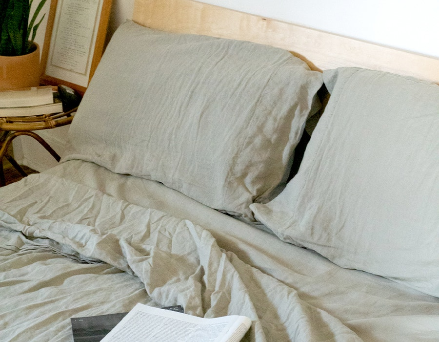a bed with Coyuchi Organic Relaxed Linen Sheets with a open magazine