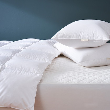 bed with down pillow on top of organic mattress pad and a three season down duvet comforter