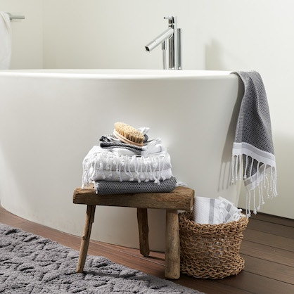 bathroom with hanging and stacked mediterranean organic towels and mosaic canyon rug