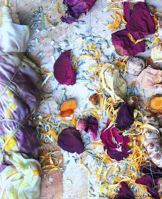 dried rose petals with flax seeds and lavender laying next to wrapped silk fabric