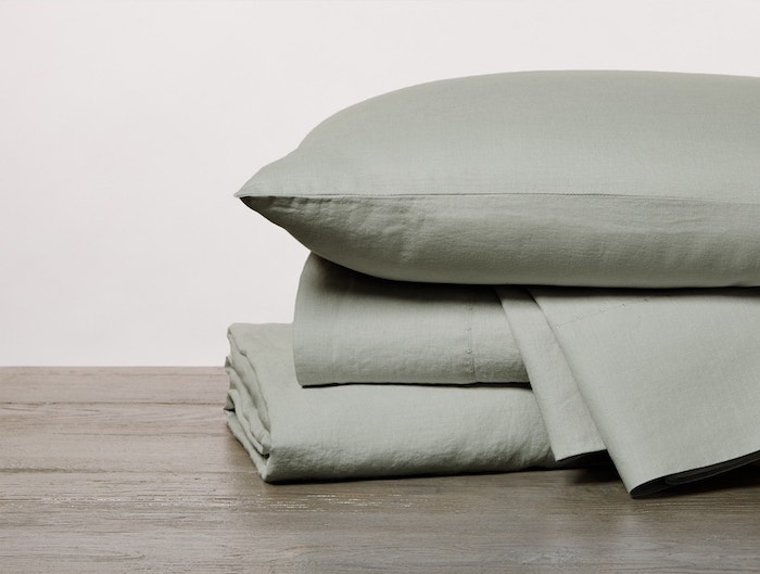 organic relaxed linen sheets stacked in laurel