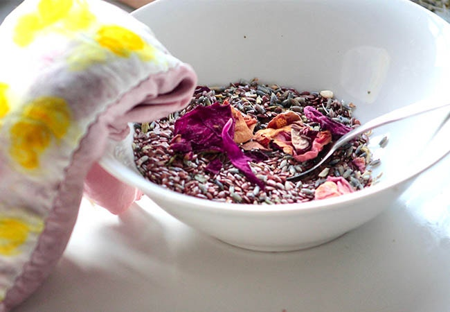 silk eye pillow resting on a bowl filled with dried rose petals, lavender, and flax seeds