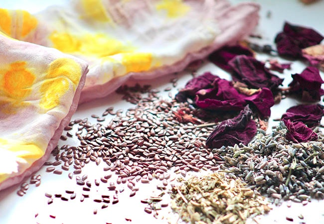 dried rose petals with flax seeds and lavender near silk fabric